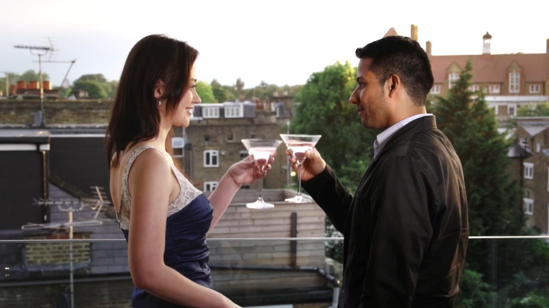 Couple celebrate with drink on balcony